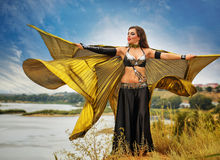 Girl dancing with golden wings. Oriental Beauty dance with wings. Nice girl in national dress dancing in the open air. Nomads. Beauty and elegance Stock Images