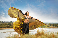 Girl dancing with golden wings. Oriental Beauty dance with wings. Nice girl in national dress dancing in the open air. Nomads. Beauty and grace Stock Photography
