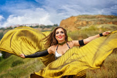 Girl dancing with golden wings. Oriental Beauty dance with wings. Nice girl in national dress dancing in the open air. Nomads. Grace Stock Photography