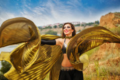 Girl dancing with golden wings. Royalty Free Stock Photos