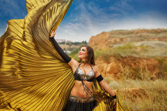 Girl dancing with golden wings. Oriental Beauty dance with wings. Nice girl in national dress dancing in the open air. Nomads. Wag wing Royalty Free Stock Photos