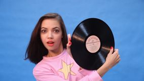 Girl dancing with a music record. On a blue background stock video footage