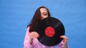 Girl dancing with a music record. On a blue background stock video