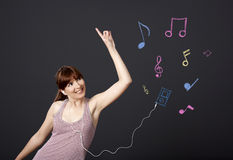Girl dancing with musical notes. Young woman dancing and listen music with musical notes drawn with chalk on a black wall royalty free stock images