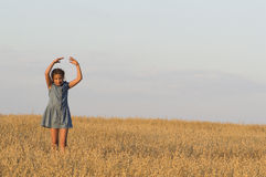 The girl is dancing in oat field. Royalty Free Stock Images