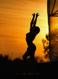 Girl dancing on the opene stage. Silhouette of young woman dancing go-go dance on the stage on the sunset against the evening sky Stock Image