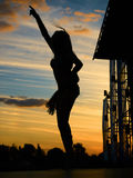 Girl dancing on the opene stage. Silhouette of young woman dancing go-go dance on the stage on the sunset against the evening sky Stock Photography