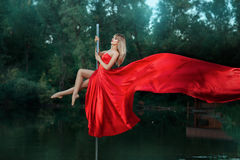 Girl dancing on a pole and her dress develops. Royalty Free Stock Images