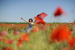 Girl dancing in poppies with flying red cloth Royalty Free Stock Images