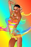 Girl dancing with ribbons on abstract background. A sexy girl dances in a multi colored bathingsuit while ribbons float around her, set against an abstract Stock Image
