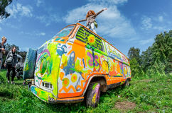 Girl dancing on the roof of colored Volkswagen Transporter Beetle on the roof Stock Photos