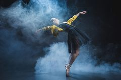 Elegant girl dancing in pointe shoes and black tutu and yellow leather jacket in studio. With smoke royalty free stock images