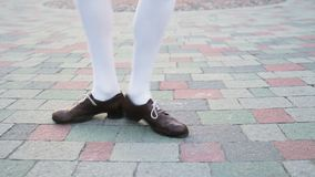 Girl dancing solo jazz swing dance. Dancer`s legs close-up. Funny dance on the city`s square pavement. stock footage