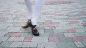Girl dancing solo jazz swing dance. Dancer`s legs close-up. Funny dance on the city`s square pavement. stock video