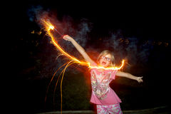 Girl Dancing With Sparkler. A dancing girl waves a sparkler through the smoke filled air like a wand on the 4th of July stock photo