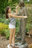 Girl dancing with a statue. Young beautiful girl posing with a statue outdoor in a park in Houston Stock Photos