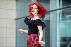 A girl is dancing on the street. Red hair. Concept of lifestyle, urban, travel, fashion.  stock photos
