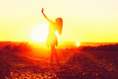 Girl dancing at sunset on the beach royalty free stock photo