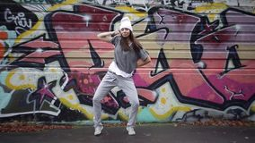 Girl dancing tectonics in the street against the background of graffiti. stock video footage