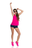 Girl Dancing Tiptoe. Shouting young woman in sunglasses, pink shirt, jeans shorts and pink sneakers standing tiptoe with arms raised. Full length studio shot Royalty Free Stock Photography