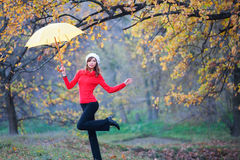 Girl dancing with an umbrella. The girl is dancing with an umbrella on one leg in the autumn park Stock Image