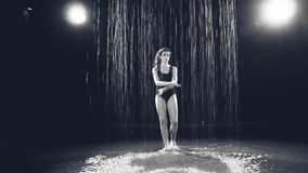 Girl dancing on the water in the studio on a black background stock video