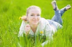 Girl on dandelion Stock Images