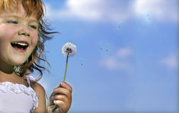 Girl with dandelion. On blue sky laugthing Stock Photo