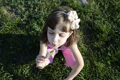 Girl with dandelion. Girl blowing on a dandelion sitting in the grass Royalty Free Stock Photography