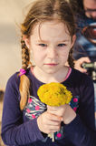 Girl with dandelion bouquet Stock Images