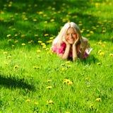 Girl on dandelion field stock images