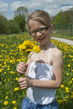 Girl and dandelion flowers. Blonde little girl smelling at some yellow dandelion flowers royalty free stock photos