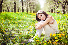 Girl in dandelion flowers. Girl is sitting in dandelion flowers royalty free stock photos