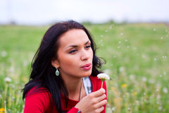 Girl with dandelion on green field. Girl blows on dandelion on green field Stock Image