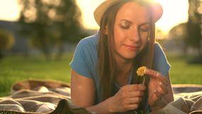 Girl with a dandelion in her hands relaxes lying down on a blanket in the park at sunset. Girl with a dandelion in her hands relaxes lying on a plaid in the park stock video