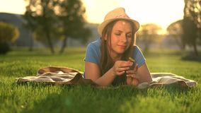 Girl with a dandelion in her hands relaxes lying down on a blanket in the park at sunset. Girl with a dandelion in her hands relaxes lying on a plaid in the park stock footage