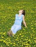 Girl on dandelion lawn Stock Images