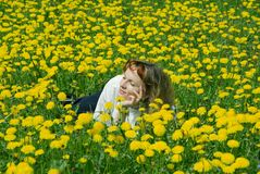 Girl on the dandelion lawn. Happy smiling girl on the dandelion  lawn Stock Photo