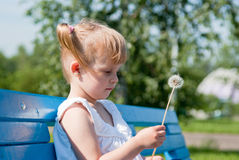 Girl with a dandelion on a park bench Royalty Free Stock Photos