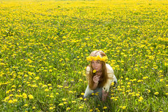 Girl among dandelions. Young pretty woman in wreath of dandelions in the meadow solar day royalty free stock photos