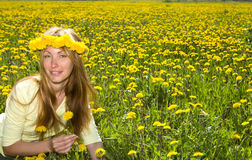 Girl among dandelions. Young pretty woman in wreath of dandelions in the meadow solar day stock photo