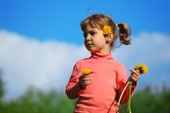 Girl and dandelions against sky Royalty Free Stock Photography