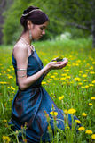 The girl in the dandelions holding a butterfly Royalty Free Stock Photos