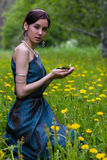 The girl in the dandelions holding a butterfly Stock Photo
