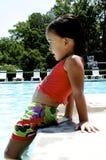 Girl dangling legs in pool Royalty Free Stock Image