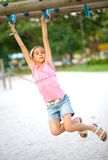 Girl dangling on playground swing Stock Image