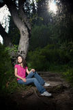Girl in a dark. Dark forest,  Girl in a dark, green wood, siting on a tree Stock Images