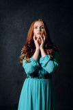 Girl on a dark background. Woman in a turquoise dress and red hair shows emotion on the dark background Stock Image