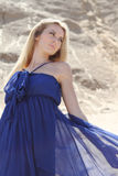 Girl in dark blue dress on the sand Royalty Free Stock Image
