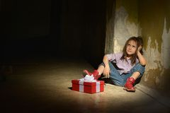 Girl  in a dark cellar with gift box Stock Images